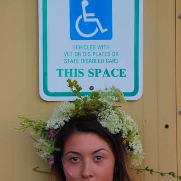 Emma, founder of Patient Perspective, poses in front of a handicap parking sign. She is wearing a crown made of flowers and smiles softly for the camera.