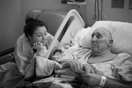 Emma sits at the bedside of her Grandpa's hospital bed. He was a disabled veteran and taught her the importance of finding strength in her story.