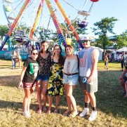 Emma's friends stand in order: Monica, Clara, Amanda, Emma, and Brian in front of a Ferris wheel. Life is a ride!